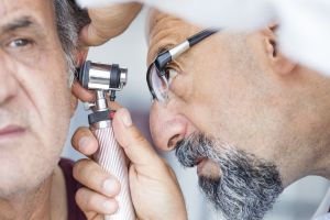 audiologist using otoscope to look into man's ear