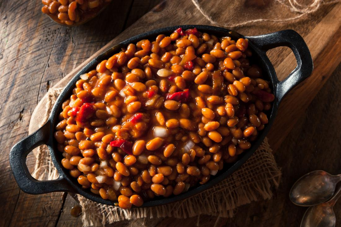 Cooked baked beans in dish on wooden table