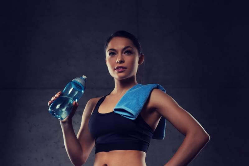 woman-with-towel-drinking-water-from-bottle