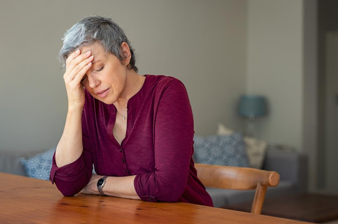 woman with a headache which is a possible side effect of naproxen