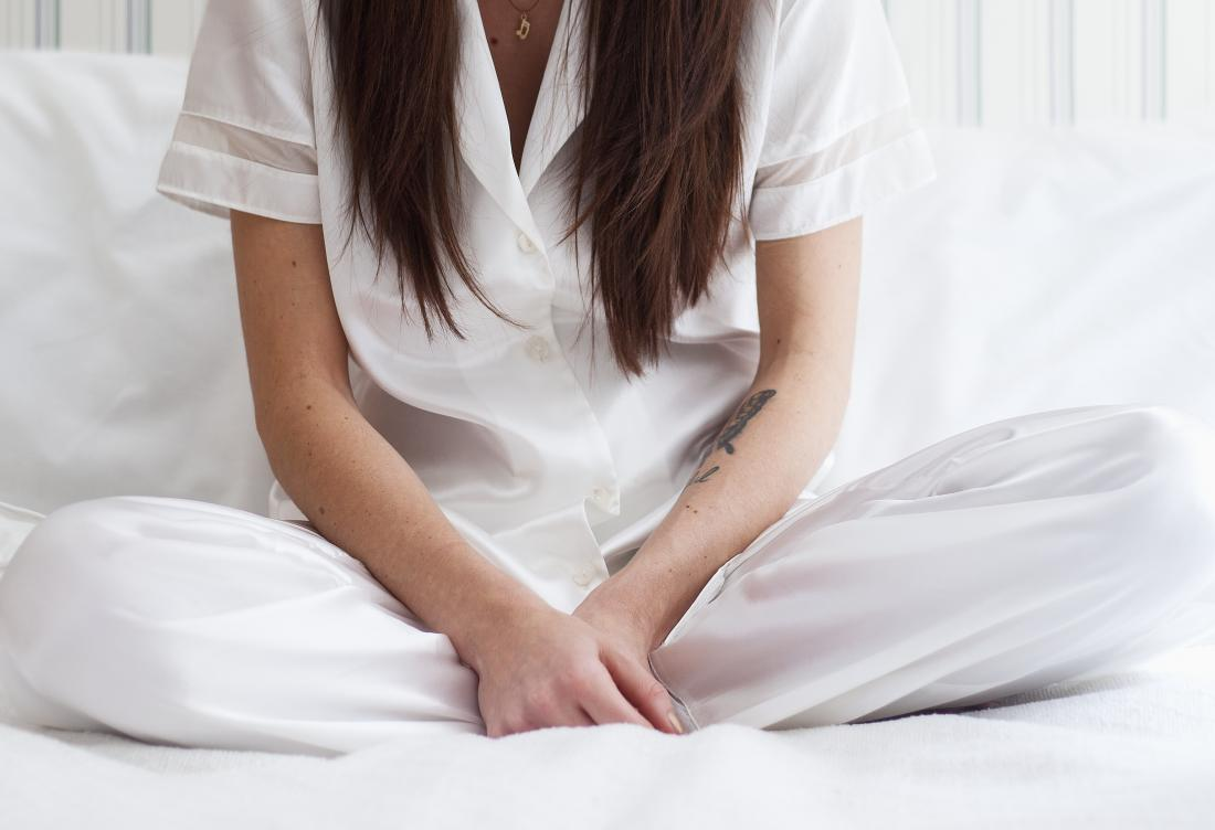 Woman with vaginal cut or tear sitting cross legged on bed