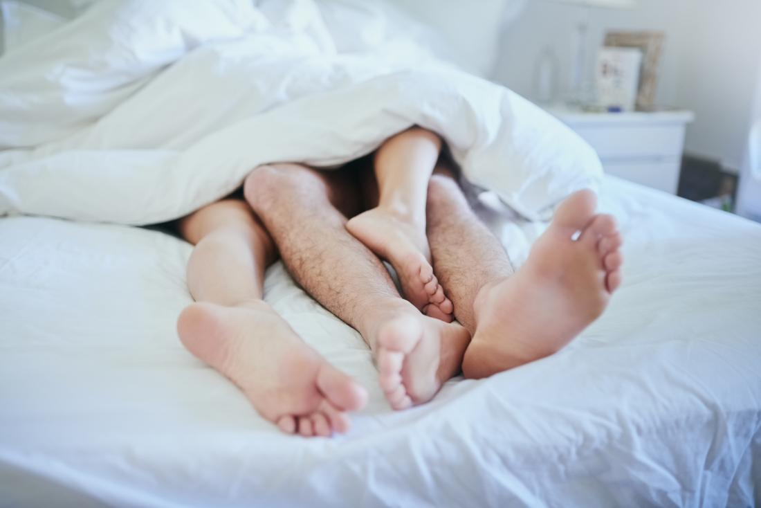 Couple in bed with feet sticking out of the duvet