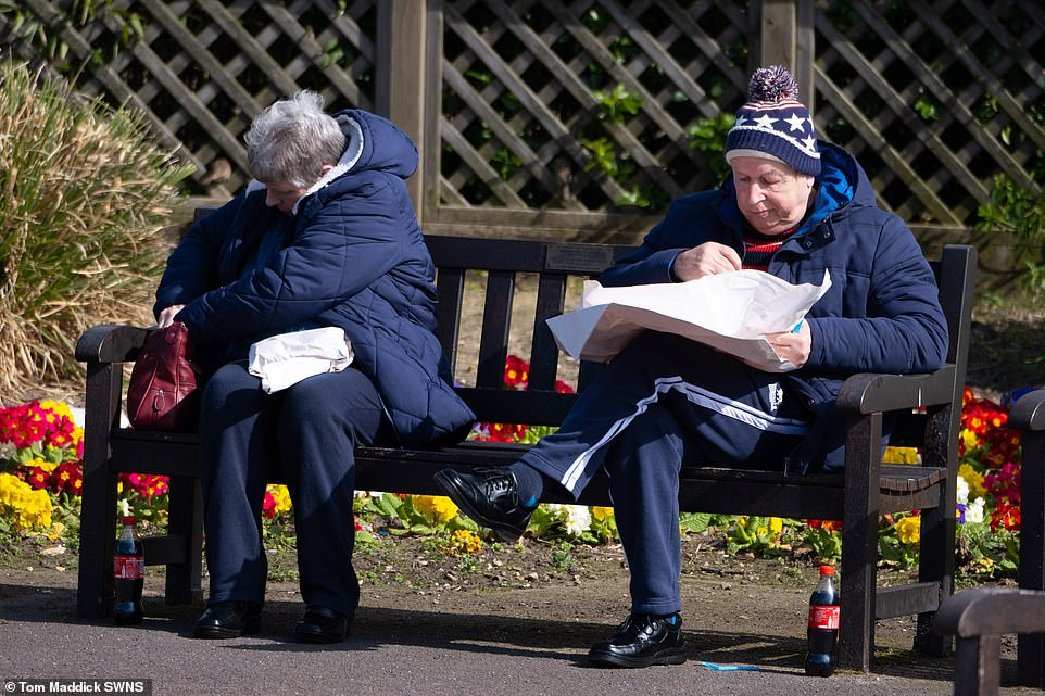People are pictured enjoying fish and chips on a bench in Skegness as crowds flocked to the resort despite warning about Covid-19