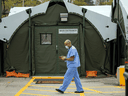 A healthcare worker walks among the tents of a field hospital set up to house patients recovering from COVID-19 at Sunnybrook Hospital in Toronto, April 28, 2021.