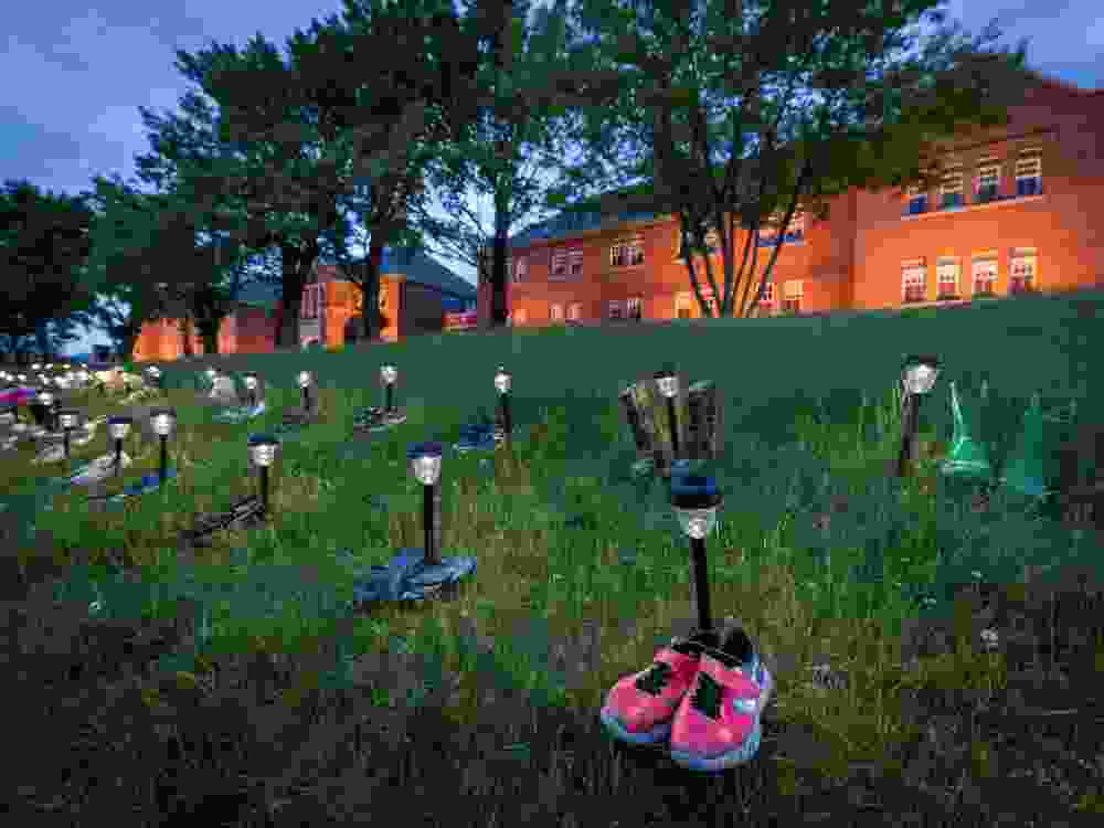 Pairs of children's shoes and toys are seen at memorial in front of the former Kamloops Indian Residential School after the remains of 215 children were found at the site last week, in Kamloops, British Columbia.